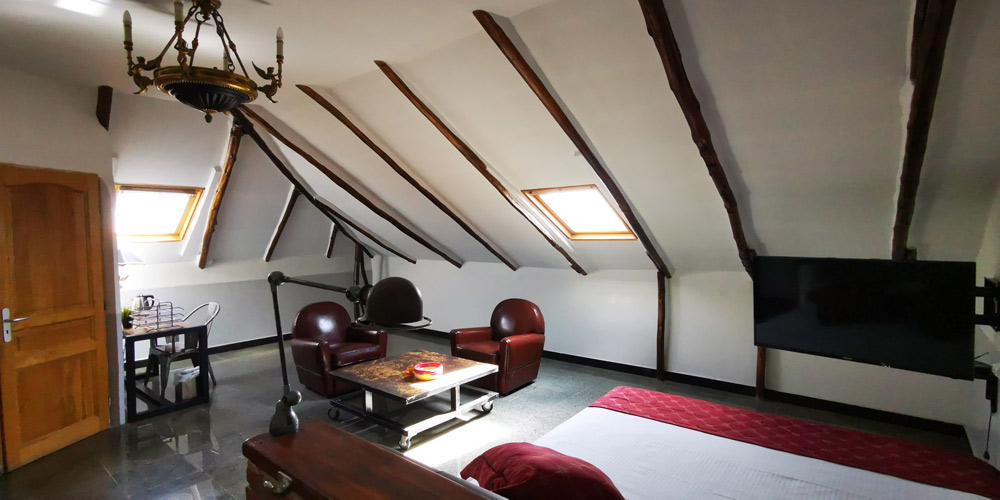 Large hotel room with sloping ceilings, with king size bed, television and living room